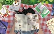 Illustrtion of a woman lying on a blanket in the grass reading books.