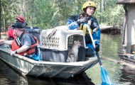 Emergency response team on a boat with rescued cats in a crate.
