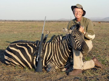 A trophy hunter props up the head of a zebra he killed for the obligatory photo.