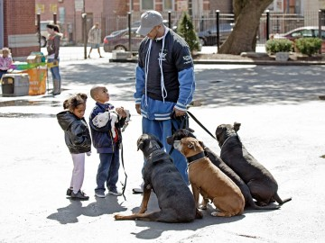 Pets for Life volunteer with dogs talking to children